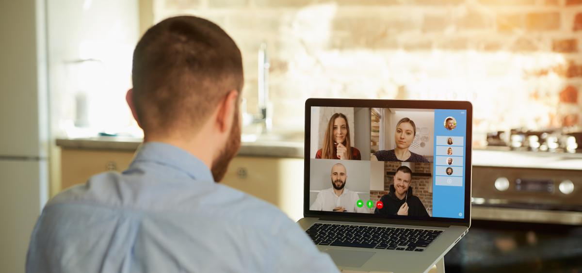 Mitarbeiter schaut auf einen Computer mit laufender Videokonferenz
